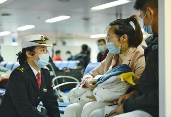 在粤海铁4号渡轮上,工作人员向抱着孩子的旅客嘘寒问暖,为旅客提供贴心服务。