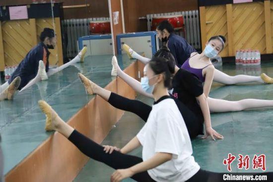 资料图:2020年,艺考生们佩戴口罩在候场室内做热身运动。 王蒙 摄