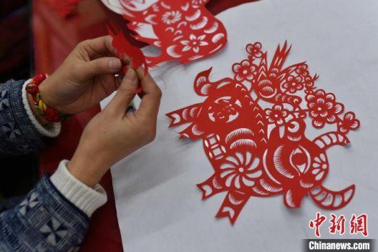 资料图:民间剪纸艺人正在创作牛年生肖剪纸 王海滨 摄