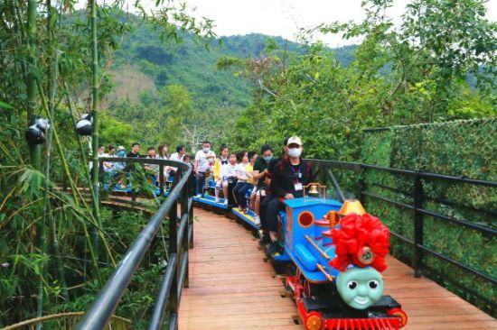 亲子家庭在槟榔谷开心乘坐空中小火车,欣赏沿途美景。潘达强摄