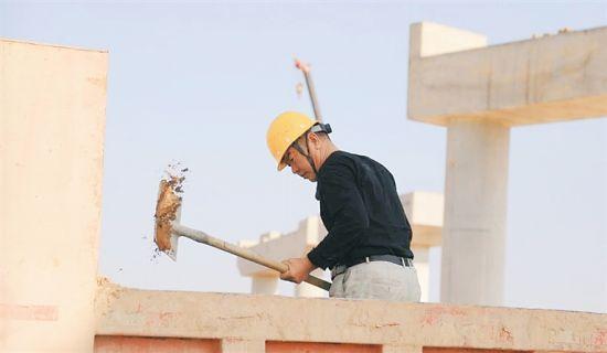 近日,国道G360文昌至临高高速公路定安段施工现场,一名工人在挥锹铲土。 通讯员 程守满 摄