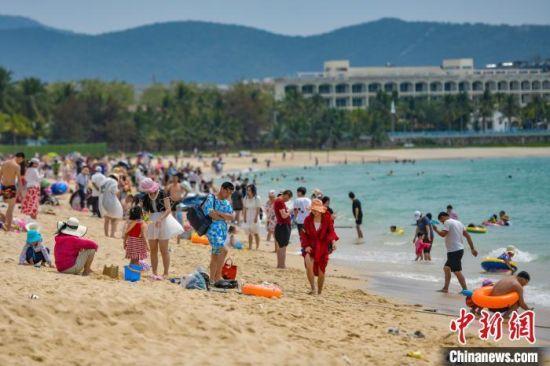 资料图。图为三亚大东海旅游景区的沙滩吸引了许多游客前来游玩。骆云飞 摄