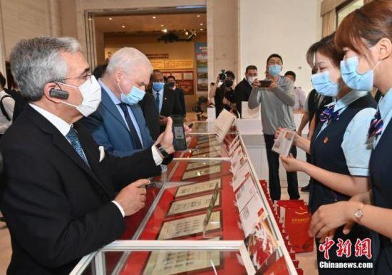 图为阿尔及利亚驻华大使艾哈桑・布哈利法(左)在展览馆内主题邮局用手机支付购买纪念邮品。 中新社记者 侯宇 摄