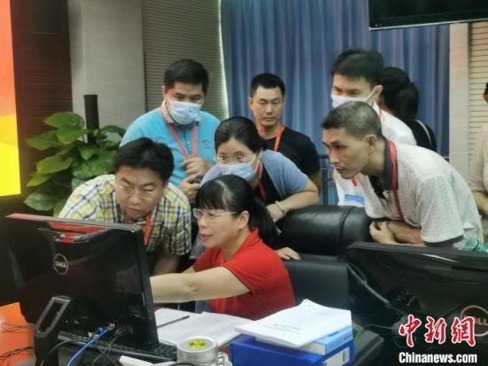 海南省考试局工作人员向前来观摩的考生、家长讲解高招录取过程。 张茜翼 摄