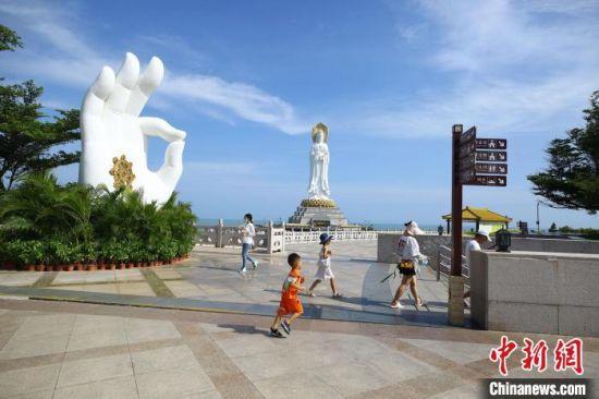8月5日,家长带着孩子在三亚南山文化旅游区游览。 陈文武 摄