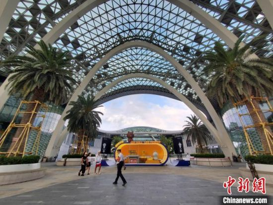 8月11日,几名顾客在三亚国际免税城空旷的广场上走过。 王晓斌 摄