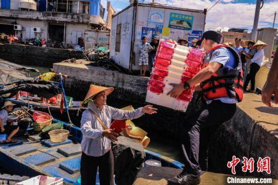 海南省公安厅海岸警察总队第七支队民警帮渔民搬箱子。 孙健 摄