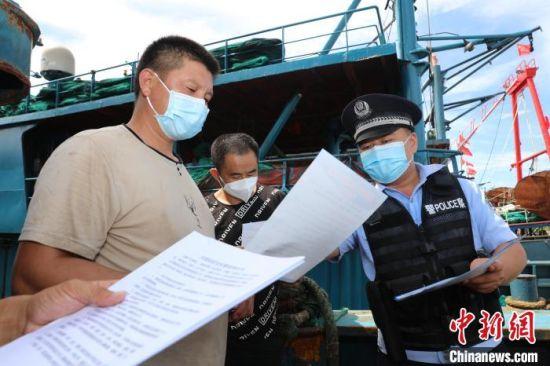 海南省公安厅海岸警察总队第四支队民警向渔民宣传防疫知识。 张春来 摄