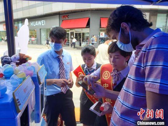 工作人员协助在三亚工作外籍人士开通数字人民币钱包。 王晓斌 摄