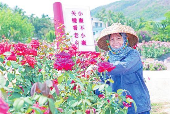 """博后村民""""斗笠大姐""""李玉梅在亚龙湾国际玫瑰谷实现了稳定就业,日子越过越红火。记者 李学仕 摄"""