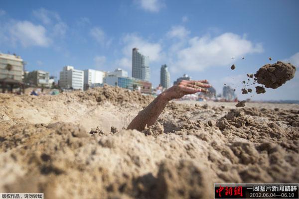 一名男子在海滩上挖沙坑