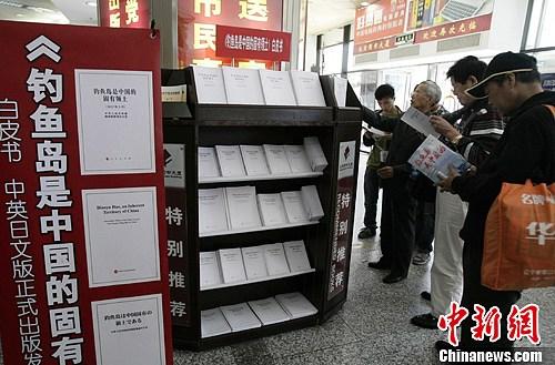 9月28日,两名拿着中国国旗的北京市民在书店阅读钓鱼岛白皮书。当日下午,《钓鱼岛是中国的固有领土》白皮书在北京西单图书大厦上架发售。中新社发 李慧思 摄