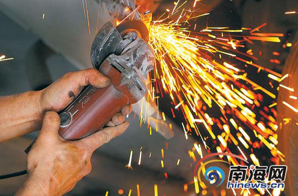 海口一家汽修厂的钣金工正在用一双有力的手打磨 ...