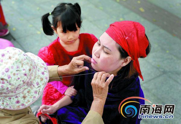 """刘孙谋/图为小女孩好奇地看着""""绞面师""""给母亲""""满面""""刘孙谋摄"""