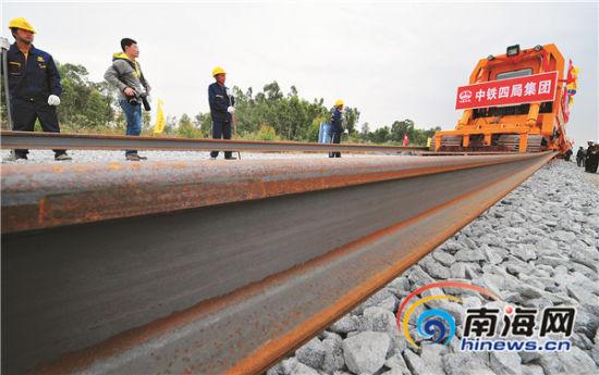 高铁东方车站有砟轨道上,一对500米长的钢轨在铺轨作业车的牵
