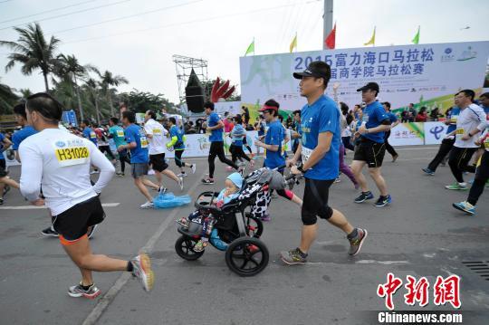 海口马拉松赛有近万人参赛,图为一位父亲推着婴儿车跑步。 骆云飞 摄