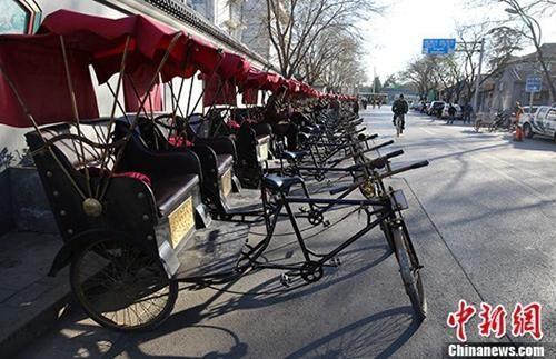 """资料图:北京什刹海附近胡同里的""""人力三轮车""""停靠在路边,排成一排。中新社发 熊然 摄"""