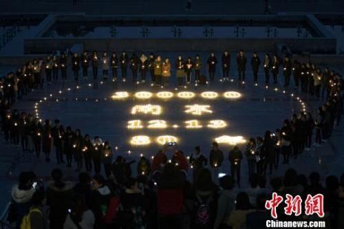2017年12月11日,南京高校学子点亮千支蜡烛,追思历史许愿和平。泱波 摄
