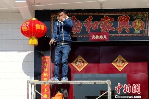 资料图:除夕,陕西关中乡村年味浓,村民挂起了灯笼。张远 摄
