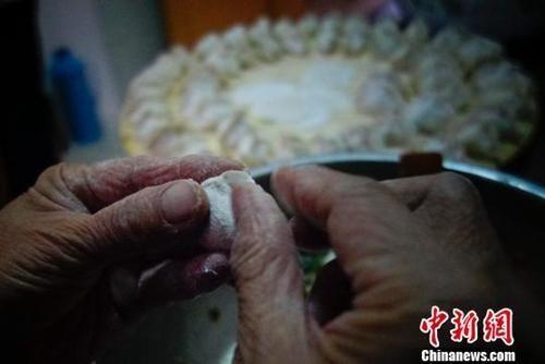 资料图:山东省蓬莱市一户家庭为除夕年夜饭包饺子。廖攀 摄