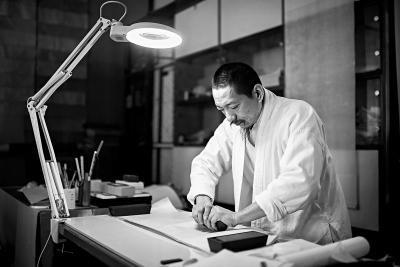 贡斌正在使用砑石对纸张进行砑光处理。 记者 邓伟摄