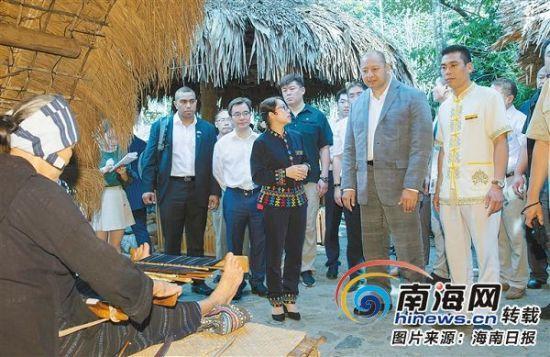 3月4日,在海南槟榔谷黎苗文化旅游区,汤加王国国王图普六世被传统的黎族手工织锦所吸引。本报记者宋国强摄