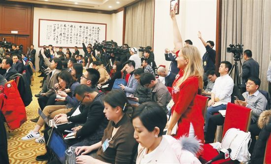 3月6日下午,参加十三届全国人大一次会议的海南代表团在驻地举行全体会议,审议政府工作报告,并举行团组开放活动,接受境内外媒体采访。图为现场参会的媒体记者踊跃举手提问。李英挺 摄