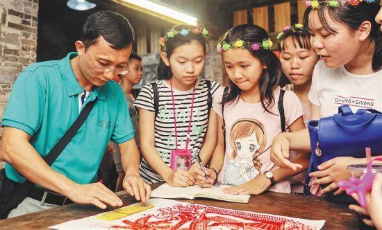 三月三日晚,琼海嘉积镇溪仔书屋里,陈瑞福(左一)给孩子们讲述传统文化知识。海南日报记者 袁琛 摄