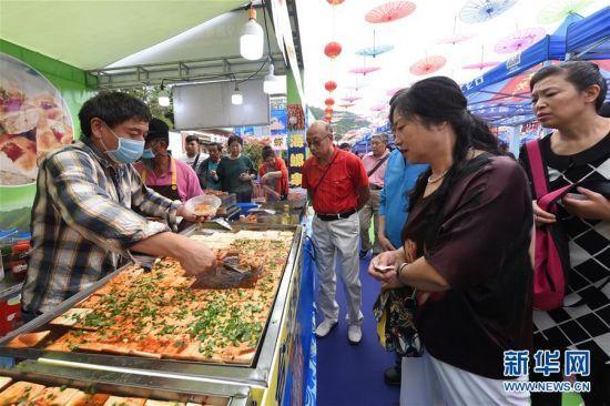 12月29日,游客在美食节上购买小吃。新华社发(张丽芸摄)