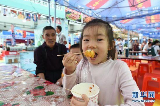 12月29日,一名小朋友在美食节上品尝美食。新华社发(张丽芸摄)