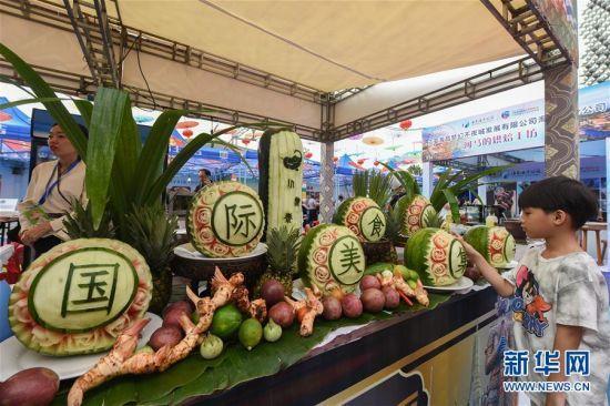 12月29日,一名小朋友在美食节上观看食雕作品。 当日,2019热带海岛(三亚)国际旅游美食节在海南三亚开幕,活动将持续至2020年1月1日。 新华社发(张丽芸摄)