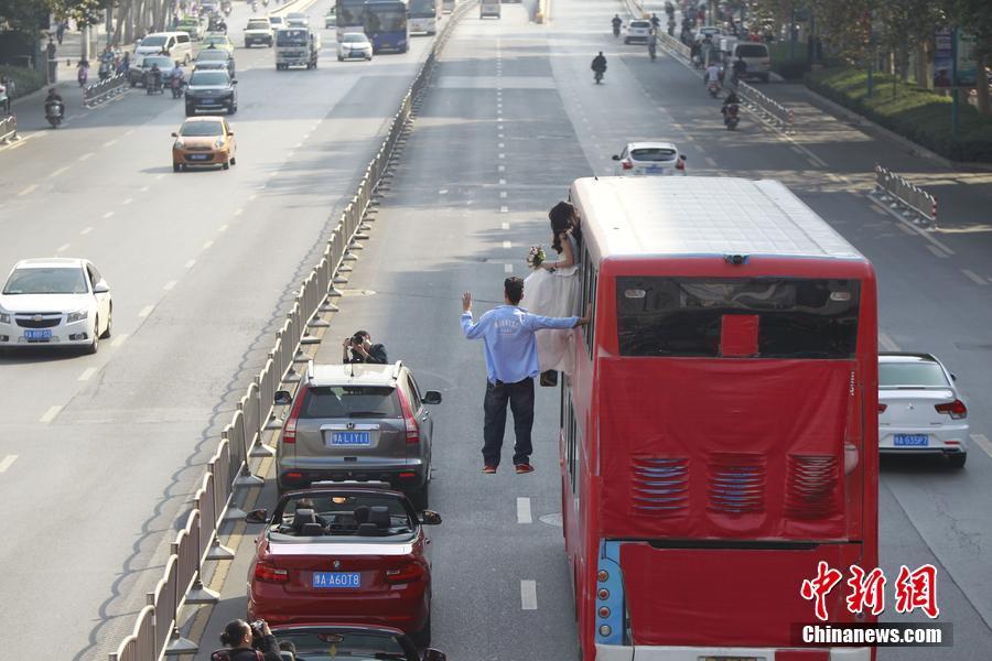 10月15日,郑州市紫荆山路,一辆行驶中的公交车外侧,一男子身高清图片