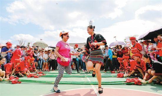 游客在陵水文罗镇坡村体验竹竿舞。